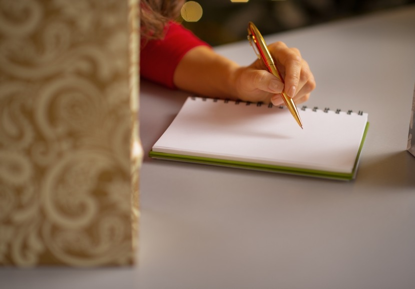 Closeup on young woman writing in notebook list of christmas purchasings